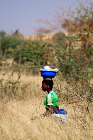 loads: the African women carrying heavy loads sometimes on their heads over long distances through the bush Editorial