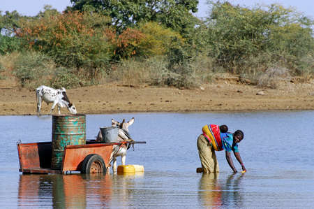 filling and transportation of water bottles at lake is for women to irrigate crops