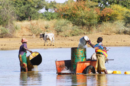 poor woman: filling and transportation of water bottles at lake is for women to irrigate crops