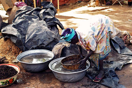 an old woman cooking local beer made from millet in Burkina Faso called Dolo in the middle of a street in Bobo-Dioulasso