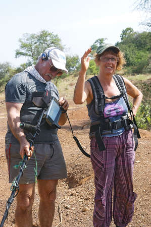 two French gold prospectors working in the African savannah in Burkina Faso, by the advice of setting the metal detector
