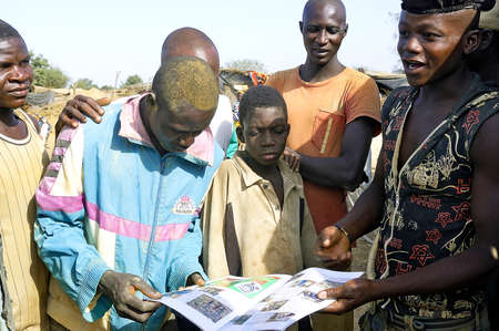 prospector: Gold miners look with surprise a review with a report on them made by a French photographer and gold prospector in Burkina Faso