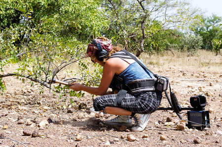 a French gold prospector at work with his metal detector in the African savannah of Burkina Faso
