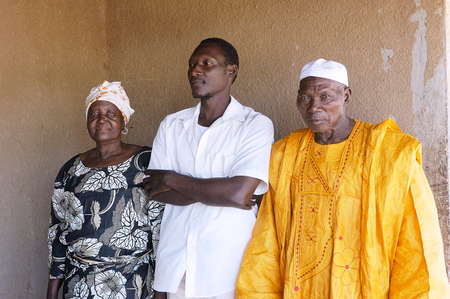 kinfolk: portrait of a son to his parents home in front of their house in Ouagadougou