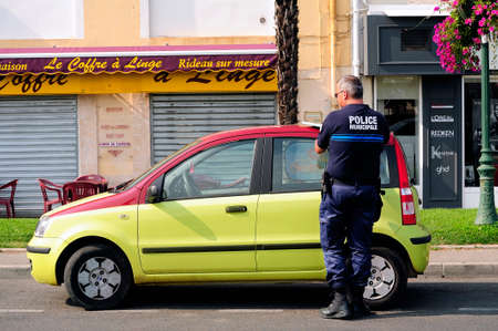 An officer of the municipal police verbalise a vehicle offense for wrong parking Editorial