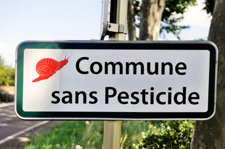 Village entry announcing the prohibition of use of pesticide for crops road sign  photo