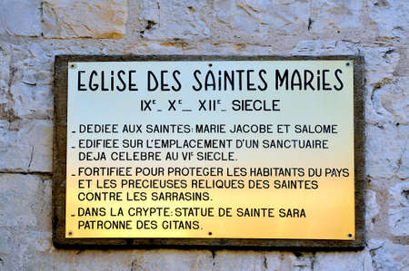 patron: plaque explaining the history of the church of Saintes-Maries-de-la-Mer. Dedicated to Saints Mary Jacobe and Salome and the Crypt containing the statue of Saint Sara patron saint of the Gypsies.