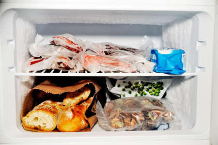 refrigerator with food: Freezer compartment of a refrigerator Containing meat and frozen vegetables as well as bread