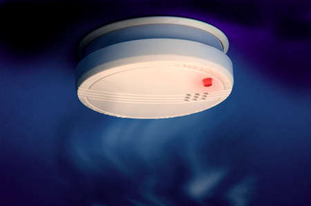 smoke detector with smoke and red light on the dark blue background