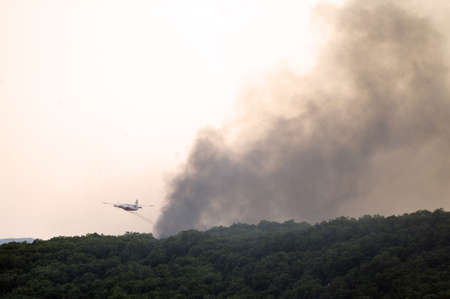 extinguishing: Tracker water bomber in the sky of southern France from extinguishing a forest fire. Stock Photo