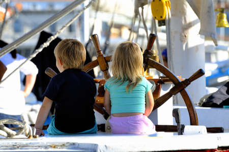Two young children on the stand of an old wooden sailing ship cruising imagining in full Editorial