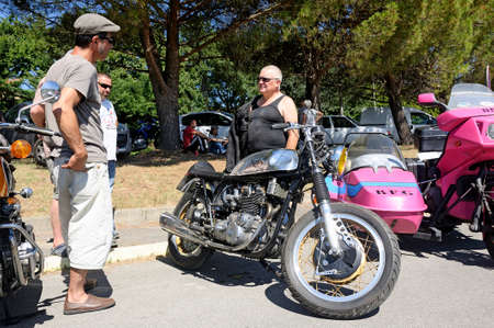 sought: motorcycle enthusiasts group around an old triumph triton is a rare and sought after model.