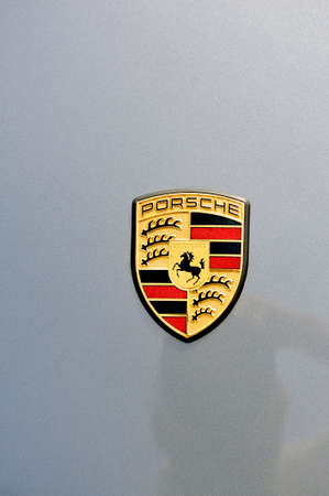 Close up on the logo of the brand of a sports car Gray porche on a parking of the city of Ales in the Gard department