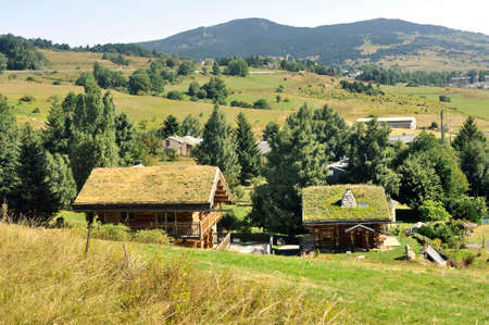 Wooden chalet with a roof with grass in a village in the Pyrenees seen from the little yellow train Redakční