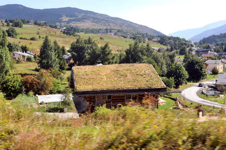 Wooden chalet with a roof with grass in a village in the Pyrenees seen from the little yellow train 新聞圖片