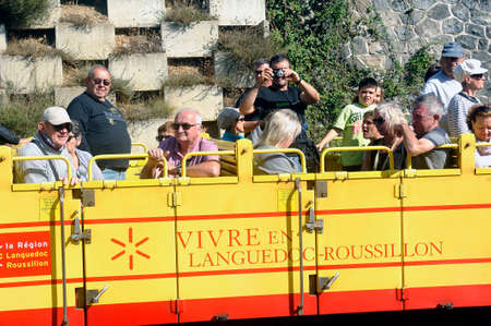 The travelers of the little yellow train of the Pyrenees in the wagon in the open air