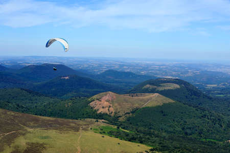 Paragliders in full flight over volcanoes of Puy de Dome in the central massif near Clermont-Ferrand