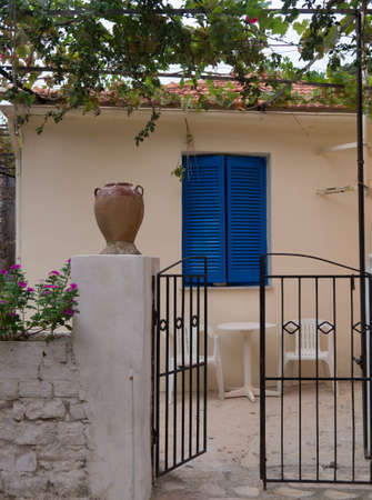 Gateway leading into a traditional house with blue shutters in Greece