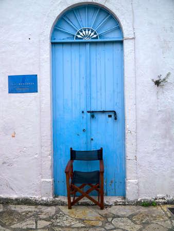 Blue door with a sunburst window above in the village of Fiskardo on the Island of Kefalonia in Greece