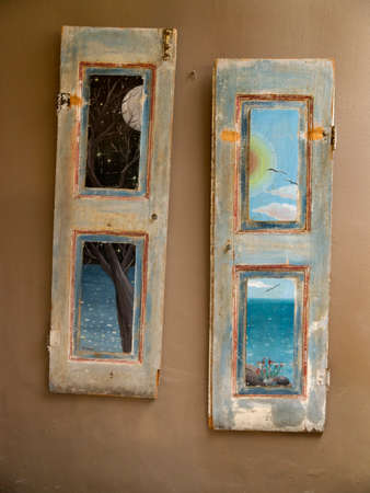 kefallonia: Artwork painted shutters hung on a cafe wall in the village of Fiskardo on the Island of Kefalonia in Greece