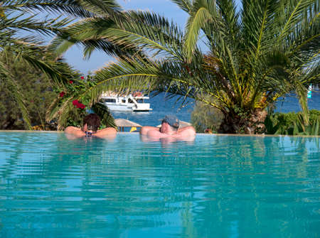 sun bathers: Relaxing in the infinity pool at the Anassa hotel on the Island of Kefalonia in Greece Editorial