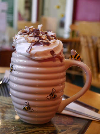 sooth: A Beehive effect drinking mug overflowing with whipped cream, chocolate and cocoa Stock Photo