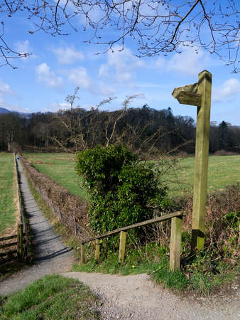 Signposted surfaced pathway towards the wooded hillock of Castlehead in the Lakeland town of Keswick Stock Photo