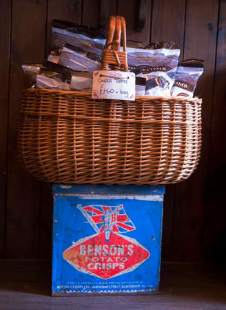 A basket full of cinder toffee sat on top of a vintage tin of Bensons  potato crisps in Mrs  Beightons sweet shop in the village of Haworth inYorkshire