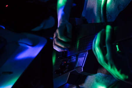 Black guitar digital synthesizer in green and purple light with hands
