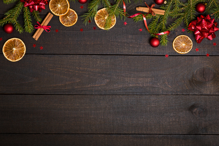 Dark rustic wooden table background with Christmas decoration and fir frame. Top view with free space for copy text Foto de archivo