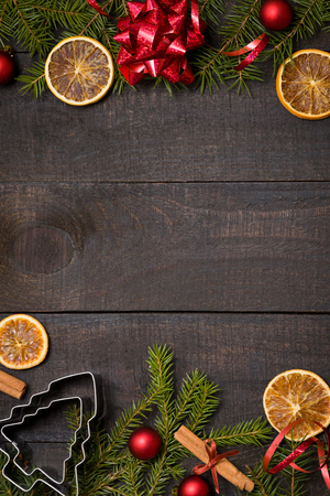 Dark rustic wood table flatlay - Christmas background with decoration and fir branch frame. Top view with free space for copy text
