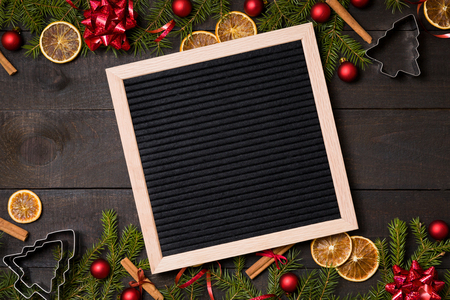 Clear black  felt letter board flatlay on dark rustic wood table with Christmas decoration and fir tree boarder. Top view with free text copy space