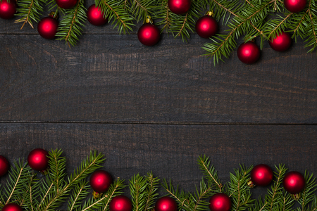 Dark rustic wood table flatlay - Christmas background with red ball ornament decoration and fir branch frame. Top view with free space for copy text