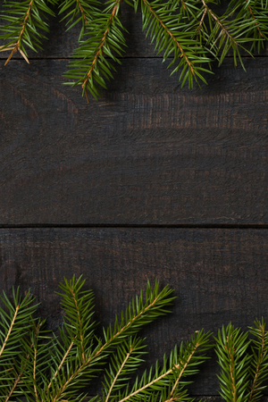 Dark rustic wood table flatlay - Christmas background with  green fir tree branch  frame. Top view with free space for copy text