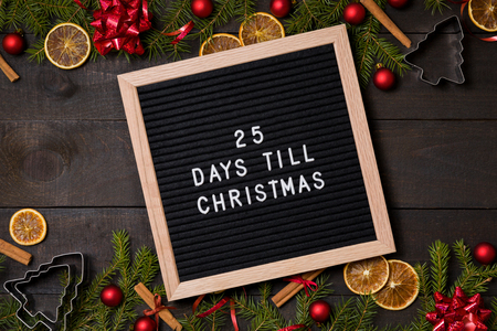 Days till  Christmas  countdown  felt letter board flatlay on dark rustic wood table with Christmas decoration and fir tree boarder