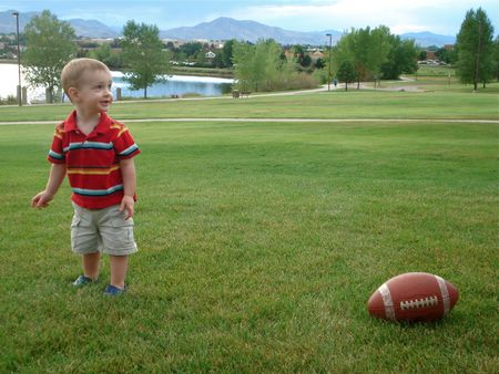 Young Boy Plays with Football at Park