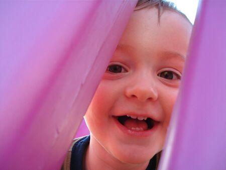 Cute Little Boy Looks Through Playground Slide