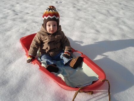 Cute Kid playing on Red Sled Stock Photo
