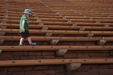 Little Boy Walking Along Stadium Seats