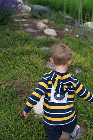 Little Boy Running Through Garden