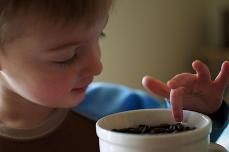 Little Boy Dipping Finger in Coffee Cup