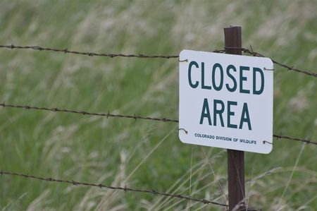Metal Sign and Barbed Wire Fence photo