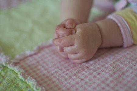 デリケートな赤ちゃんの手と毛布