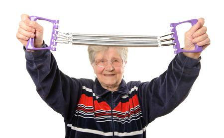 espander: Senior woman exercising isolated on white