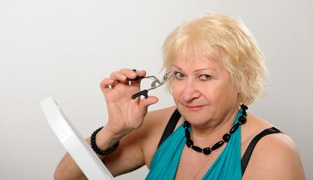 curler: Woman using eyelash curler.