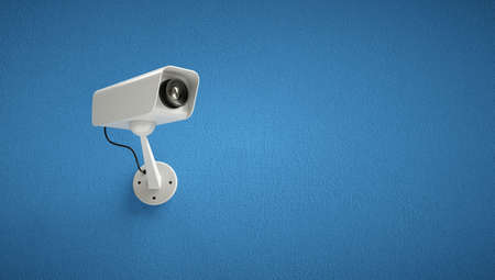 Security camera watching over blue wall.