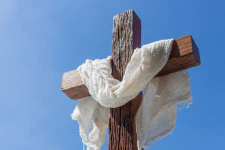 Wooden cross with a white cloth in front of a blue sky