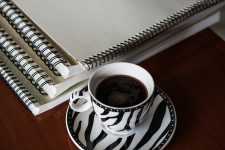 Background for vintage with white sketchbook with cup of coffee on wooden desk