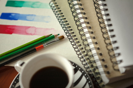 Colored pencils and paintbrush on a wooden desk and colored sketch Abstract background with coffee