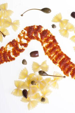 puttanesca: Farfalle pasta puttanesca decomposed on white background